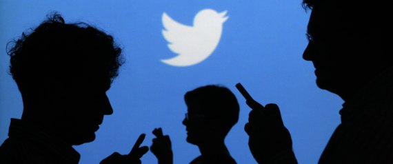 People holding mobile phones are silhouetted against a backdrop projected with the Twitter logo  in Warsaw